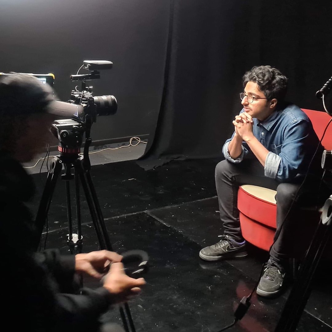 Harsha sits in a red chair and leans forward, he's being filmed in a black room with a guy in a black baseball cap